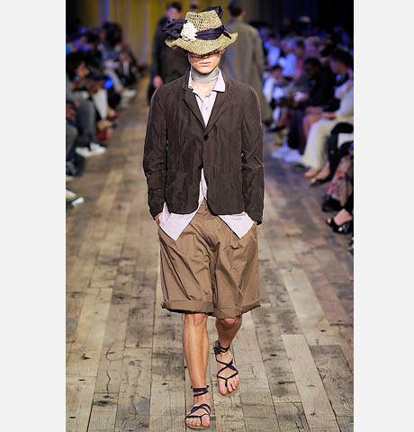 Lanvin açık kahverengi erkek şort, koyu kahverengi ceketi sandalet ve koloniyel hasır bir şapka ile tamamlamış