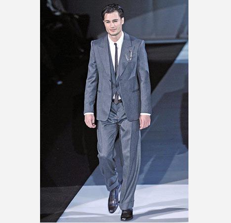 Gri yelekli dar kesim bu takım elbise ince bir kravat ile tamamlanmış
