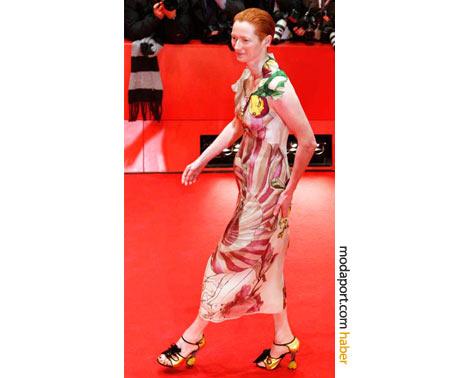 Tilda Swinton, bu Prada saten elbise ve sarı Prada ayakkabılarla, her zamanki tarzından daha yumuşak hatlı bir stil benimsemiş. Berlin Film Festivali 2008