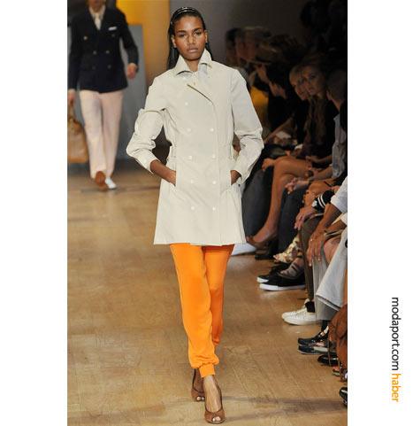 """Trençkotun altındaki turuncu ipek eşofman altı, Tommy Hilfiger'ın sözlerini özetliyor: """"Haute Couture koleksiyon, 70'li ve 80'li yılların başında hakim olan parlak ve göz alıcı Amerikan spor giyiminden ilham alıyor,"""""""
