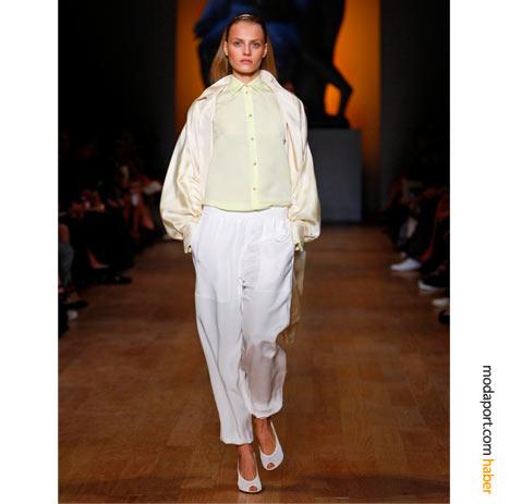 Beyaz ince pantolon, sarı gömlek ve ipek mont, sıradışı bir spor giyim stili