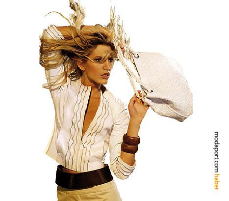 Kumaş pantolonun üstüne giyilmiş ince, işli deri ceket gömlek hafifliğinde. Beyaz deri çanta ise, doğal tonlarla uyum gösteriyor.