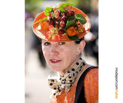 Carole Denford, meyvelerle süslü turuncu hasırdan Marie Mercie şapka modeliyle