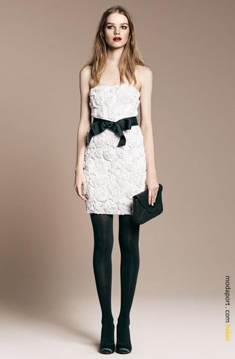 Straplez beyaz elbise, trende uygun olarak siyah çorapla giyiliyor.