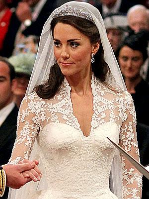 Dantelden yüksek V yakalı gelinlik, güncel bir Viktoria stiline sahip. Tacı, kraliçe ödünç vermiş.